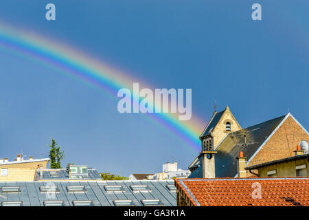 rainbow over a church roof - Stock Photo