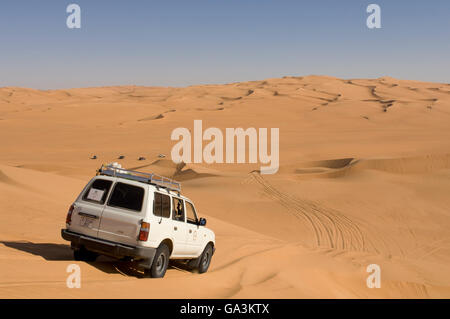 SUV on sand dunes, Erg Awbari, Sahara desert, Fezzan, Libya, North Africa - Stock Photo