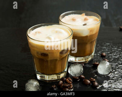 Iced coffee in glasses with ice cubes and coffee beans - Stock Photo
