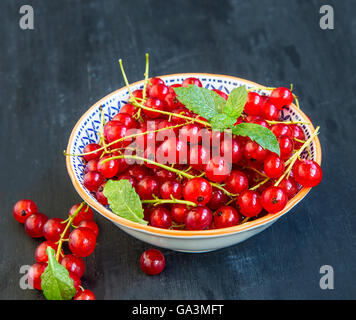 Red fresh currants in a rustic bowl with mint leaves - Stock Photo