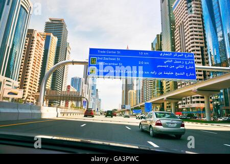 City of Dubai. Road signs driving along city centre Sheikh Zayed Road. Al Yaquob Tower in distance. United Arab - Stock Photo