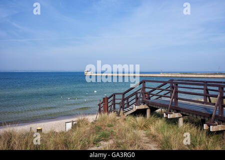 Poland, Pomerania, Hel Town, Puck Bay at Baltic Sea, grassy dune with boardwalk to the beach and pier - Stock Photo