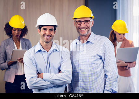 Portrait of two architects standing with arms crossed in office - Stock Photo