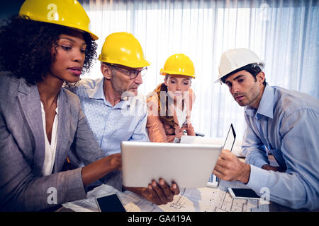 Architects discussing over digital tablet in office - Stock Photo