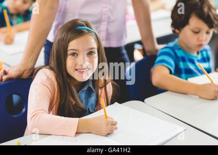 School girl doing homework in classroom - Stock Photo