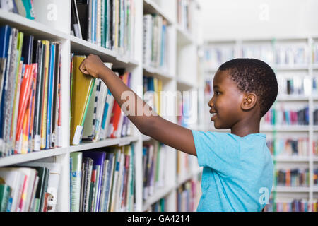 Schoolboy selecting a book from bookcase in library - Stock Photo
