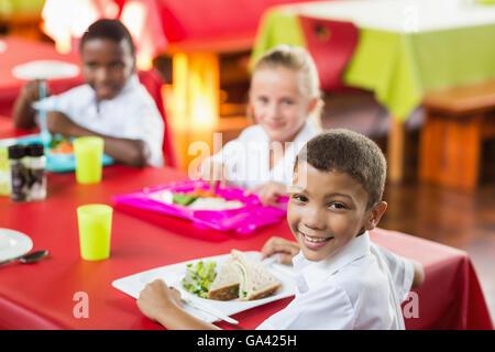 Children having lunch during break time in school cafeteria - Stock Photo