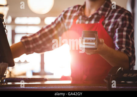 Mid section of waiter showing credit card machine - Stock Photo