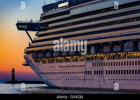 Princess Cruises' 'Emerald Princess' leaving the harbour of Rostock-Warnemünde, Germany during sunset. - Stock Photo