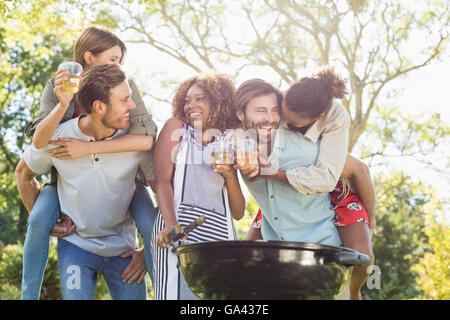 Men giving piggyback to women while preparing barbecue in park - Stock Photo
