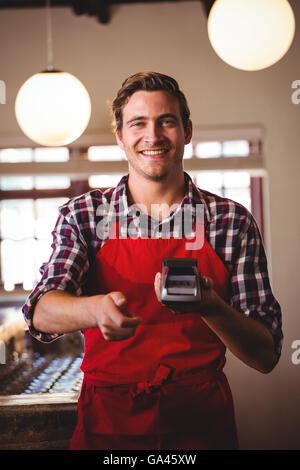 Portrait of waiter showing credit card machine - Stock Photo