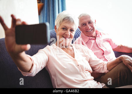 Smiling senior couple taking a selfie - Stock Photo