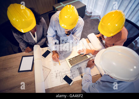 Four architects discussing blueprints in meeting - Stock Photo