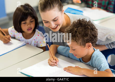 teacher helping schoolchildren to write on book - Stock Photo