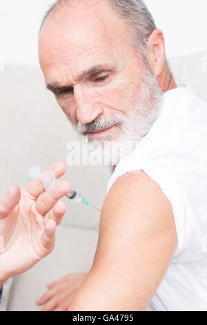 Senior man observing while being vaccinated - Stock Photo