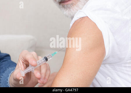 Senior man looking on being vaccinated - Stock Photo