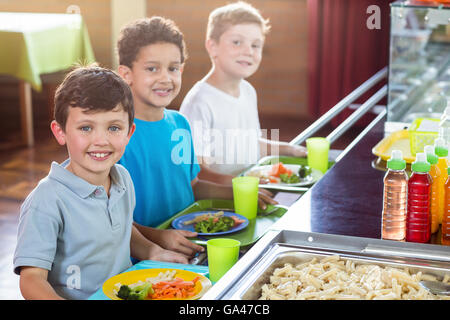 Schoolboys standing near counter - Stock Photo
