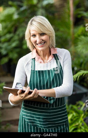 Female gardener writing in clipboard at greenhouse - Stock Photo