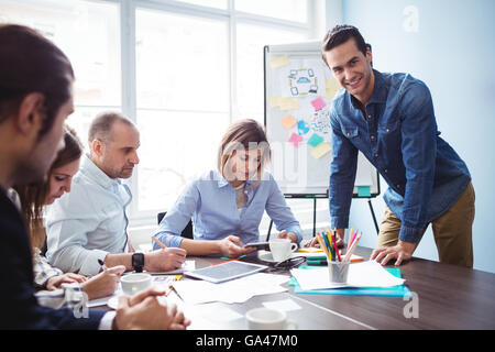 Smiling businessman with coworkers in meeting room - Stock Photo