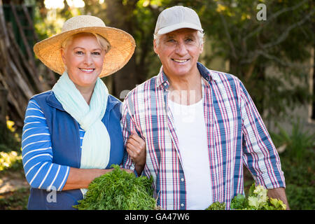 Portrait of happy couple with vegetables at garden - Stock Photo