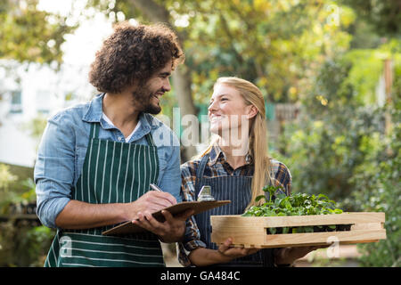 Woman holding plants in crate while gardener writing on clipboard - Stock Photo
