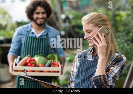 Female gardener talking on cellphone while man in background - Stock Photo