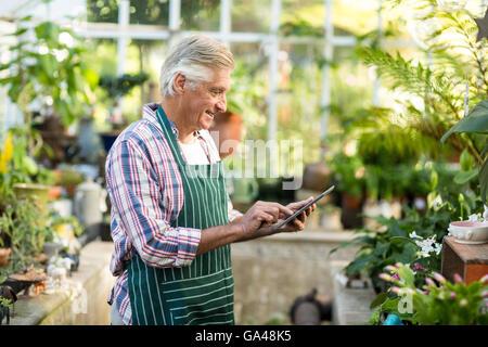 Mature man using digital tablet at greenhouse - Stock Photo