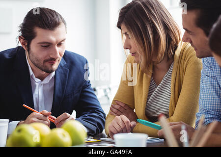 Photo editor explaining to colleagues in meeting room - Stock Photo
