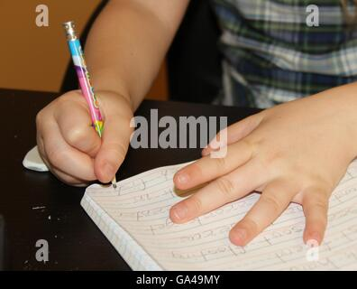 elementary girl hands doing school homework with a used pencil in a desk - Stock Photo