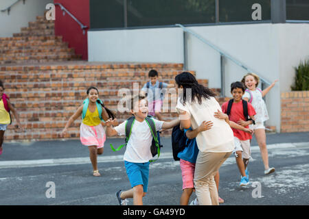 Happy children running towards teacher - Stock Photo