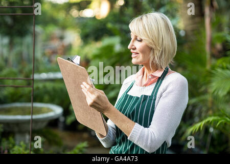 Female gardener writing in clipboard - Stock Photo