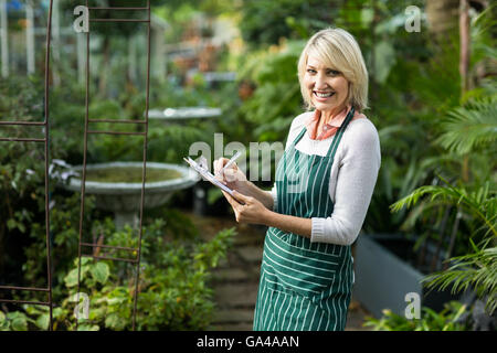 Portrait of female gardener writing in clipboard - Stock Photo