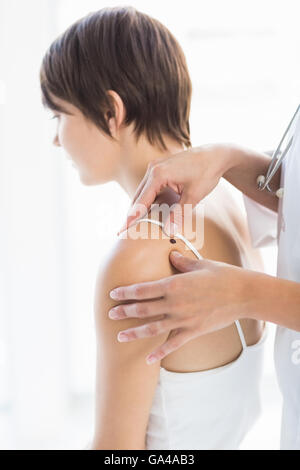 Cropped image of doctor examining woman - Stock Photo