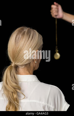 Cropped hand of hypnotherapist holding pendulum by woman - Stock Photo