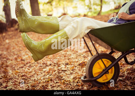 Low section of gardener sitting in wheelbarrow at garden - Stock Photo