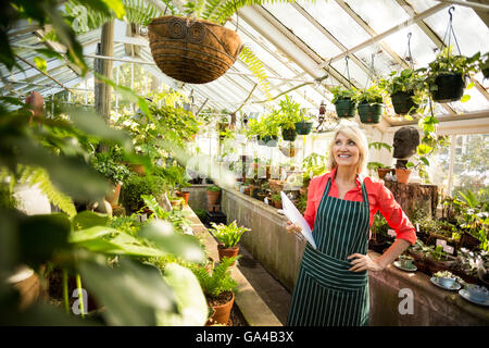 Woman looking at plants hanging in greenhouse - Stock Photo