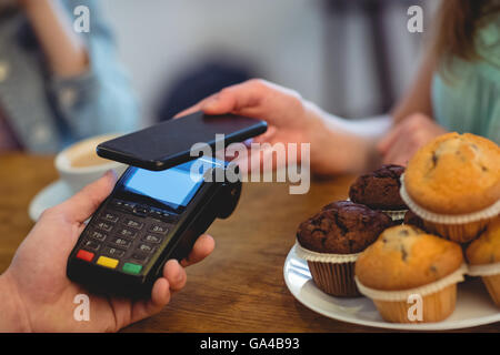 Cropped image of barista and customers using technologies at cafe - Stock Photo