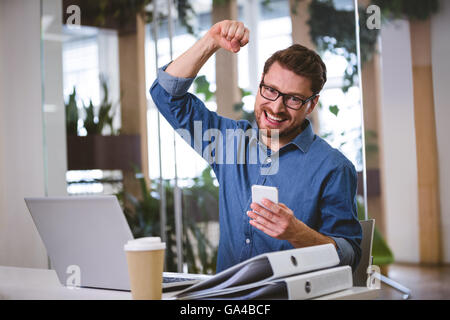 Portrait of excited businessman punching in air at office - Stock Photo
