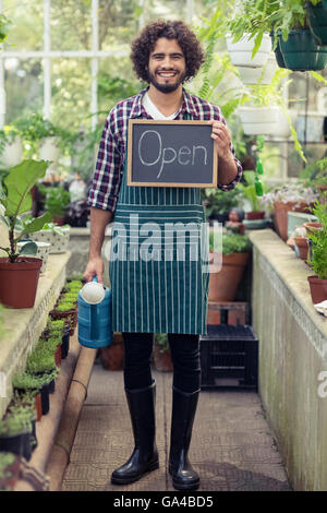 Male gardener holding open sign placard and watering can - Stock Photo