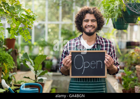 Happy bearded gardener holding open sign placard - Stock Photo