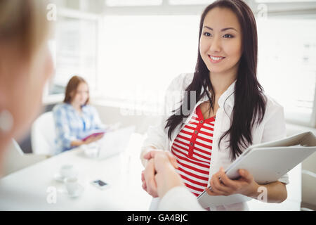 Businesswoman shaking hands with partner in creative office - Stock Photo