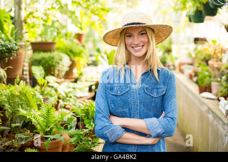 Young female gardener at greenhouse - Stock Photo