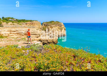 Spring flowers in foreground with young woman tourist standing on cliff rock and looking at sea, Portugal - Stock Photo