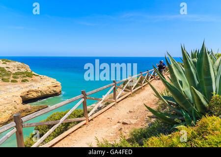 Tourists on cliff path along sea watching beautiful sea bay near Carvoeiro town, Portugal - Stock Photo