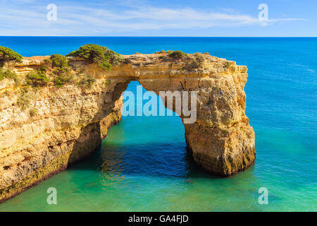 Rock cliff arch near Marinha beach and blue sea on coast of Portugal in Algarve region - Stock Photo