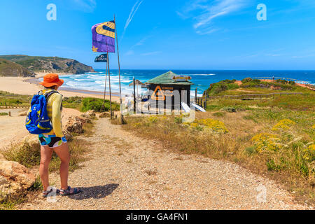 AMADO BEACH, PORTUGAL - MAY 15, 2015: Young woman tourist on walking path to Praia do Amado beach in spring, Algarve - Stock Photo
