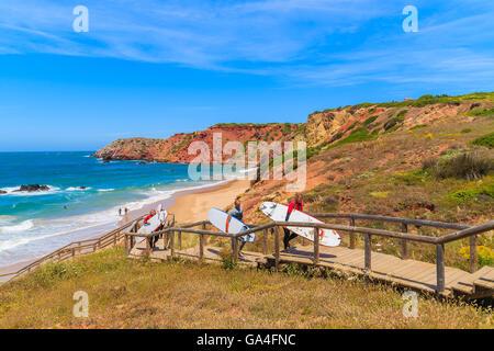 PRAIA DO AMADO BEACH, PORTUGAL - MAY 15, 2015: surfers walking on footbridge from beautiful beach in Algarve region. - Stock Photo