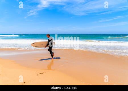 PRAIA DO AMADO BEACH, PORTUGAL - MAY 15, 2015: Surfer walking on Praia do Amado beach with ocean waves hitting shore, - Stock Photo