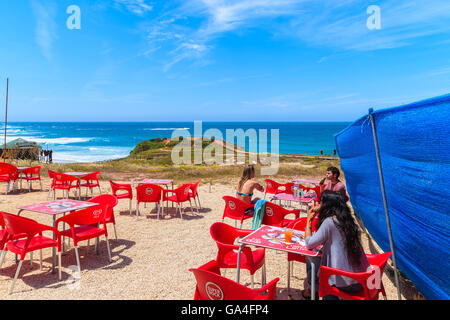PRAIA DO AMADO BEACH, PORTUGAL - MAY 15, 2015: tourists sitting in a cafe on Praia do Amado beach with ocean in - Stock Photo