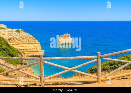 Wooden fence on cliff path on coast of Portugal in Algarve region near Praia de Marinha beach - Stock Photo